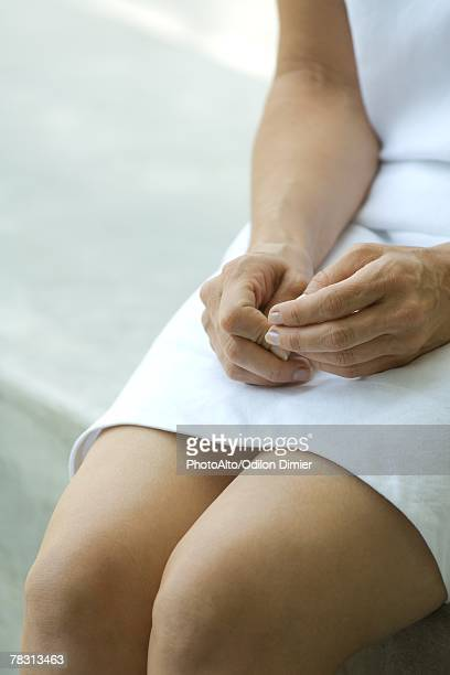 woman sitting with hands on legs, cropped view - mid section stock photos and pictures