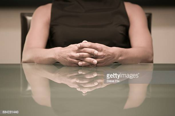 woman sitting with hands together - sleeveless stock pictures, royalty-free photos & images