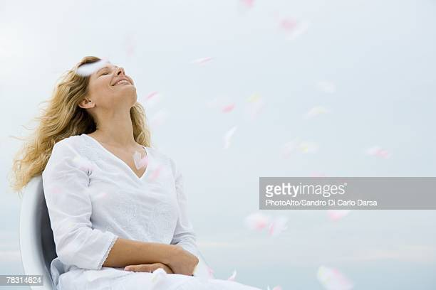 Woman sitting with head back and eyes closed among floating flower petals
