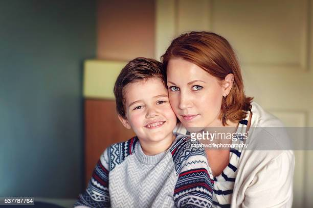 Woman sitting with her five year old son in a bedroom