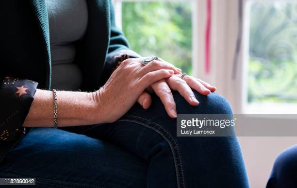 woman sitting with her hands on her knee, listening - medium shot stock pictures, royalty-free photos & images