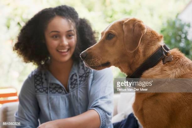 Woman sitting with labrador retriever dog on sofa.