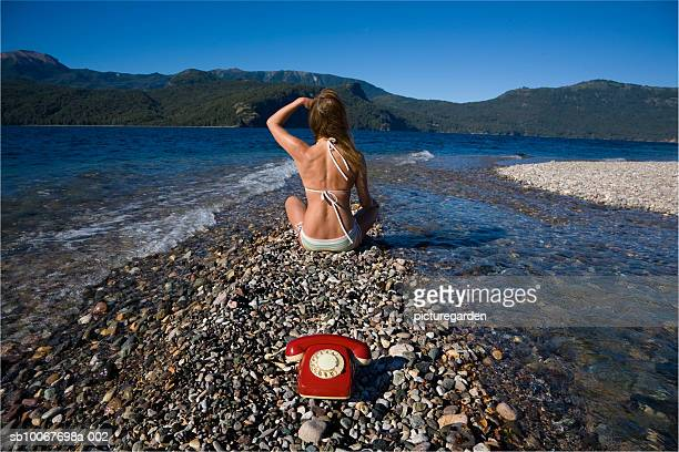 Woman sitting with landline phone at lakeside, rear view