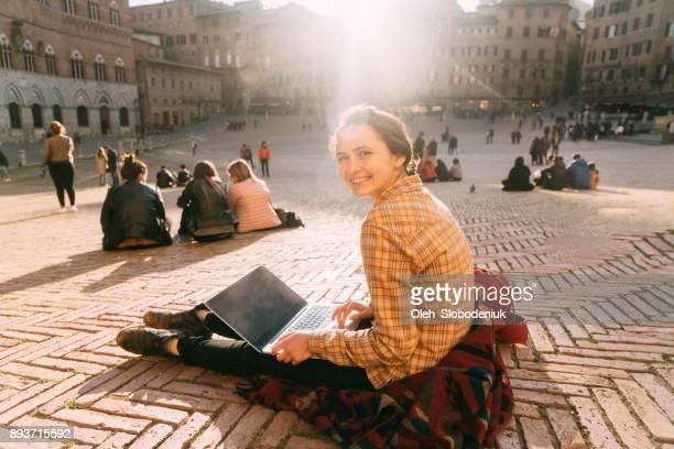 donna seduta con portatile in piazza del campo a siena - piazza foto e immagini stock