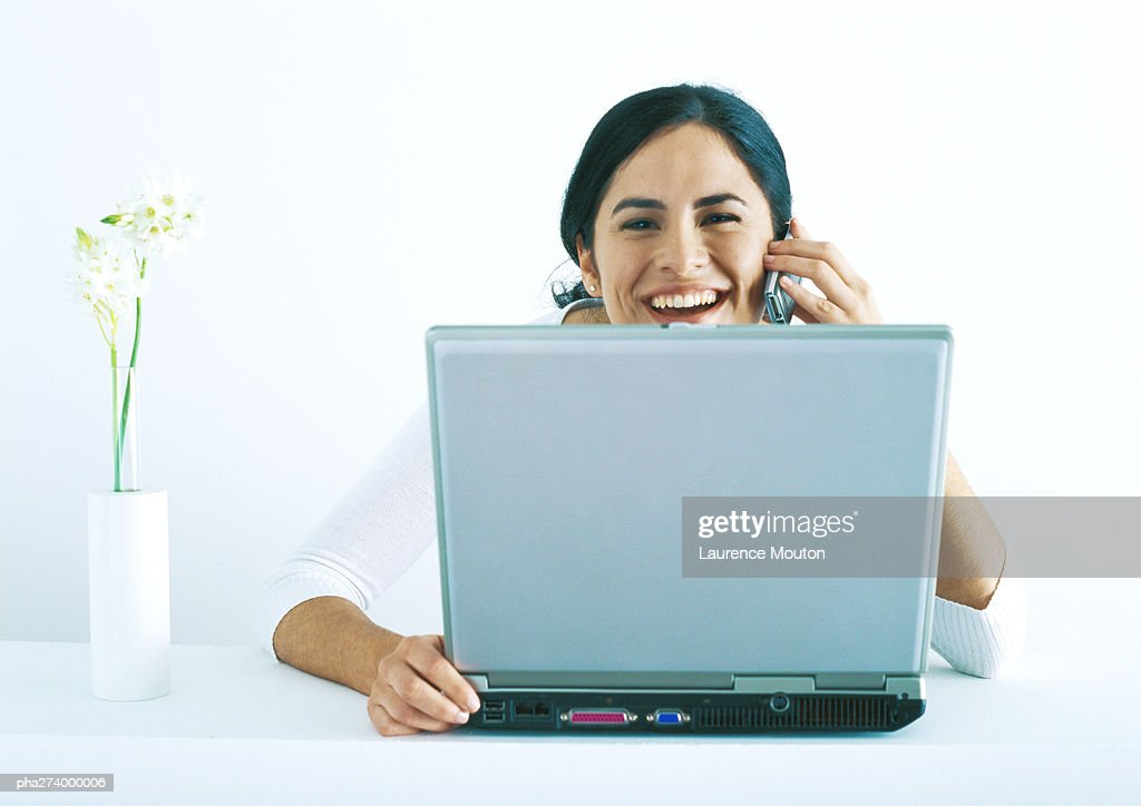 Woman sitting with laptop, talking on phone and laughing : Stockfoto