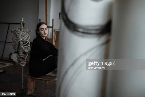 Woman sitting with skeleton in artists studio