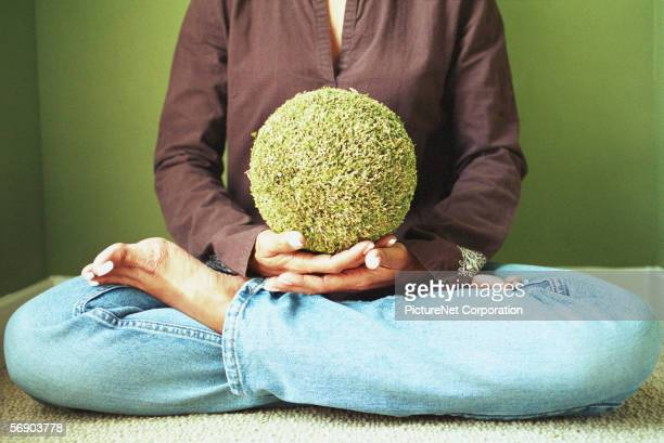 Woman sitting with turf ball