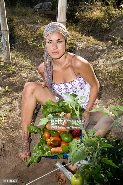 Woman sitting with vegetables in a field, Tucuman, Argentina