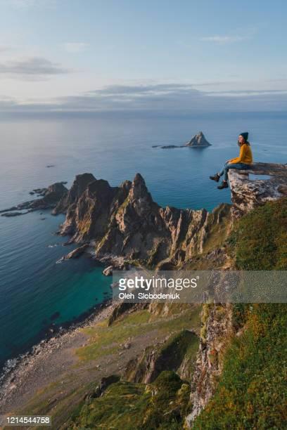 de zitting van de vrouw met mening op kust op eiland lofoten - noorwegen stockfoto's en -beelden