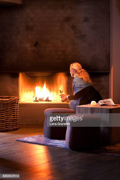 Woman sitting with wineglass and looking at fireplace