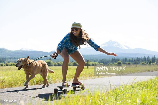 A woman skateboarding with her dog.