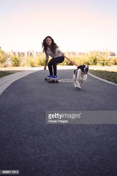 Woman skateboarding with running dog on street against clear sky