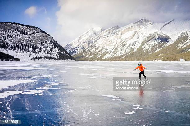 Woman skates across frozen lake, in mountains