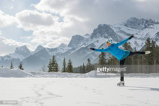 Woman skates on frozen pond under snowy mountains