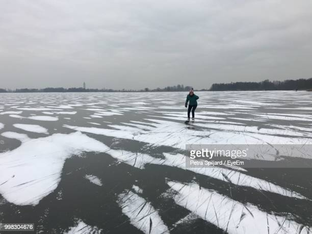 Woman Skating On Ice Rink Against Sky