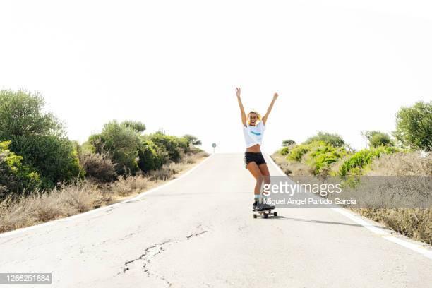 woman skating with her arms up. - eislauf oder rollschuhlauf stock-fotos und bilder