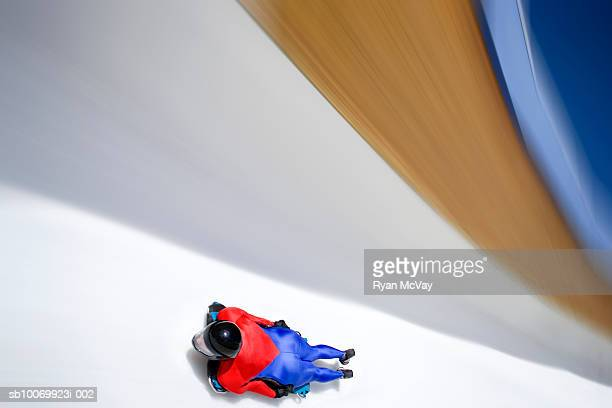 Woman Skeleton athlete on sled racing down ice track, blurred motion, low angle view