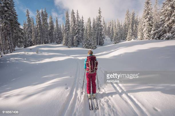 Woman ski touring on snow-capped forest path