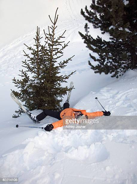 woman skier lying on her back by tree - ski humour photos et images de collection
