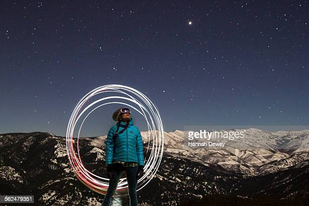 Woman skier standing under a starry night sky in Montana.