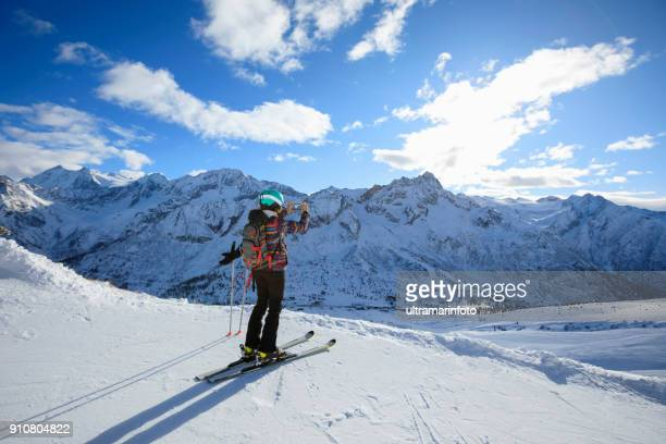 woman skier using smartphone at sunny ski resort amateur winter sports on the top - female skier stock pictures, royalty-free photos & images