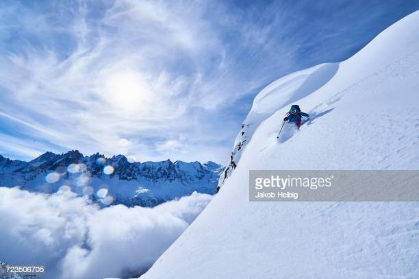woman skiing down steep mountainside in swiss alps, gstaad, switzerland - グスタード ストックフォトと画像