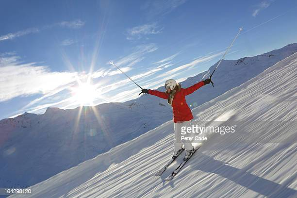 Woman skiing downhill, blue sky, sun shining