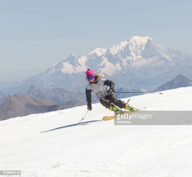 Woman skiing downhill snow-capped slope