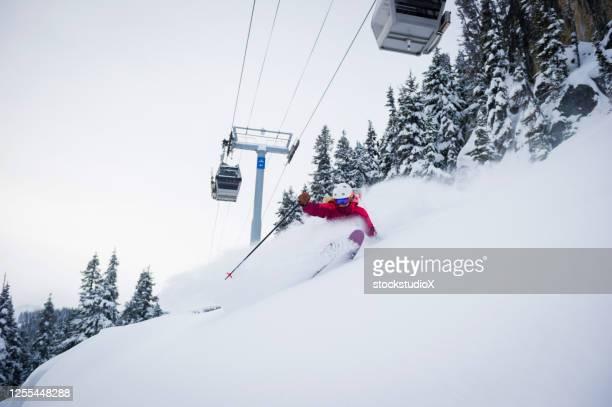 スキー休暇で新鮮なパウダーをスキーする女性 - アルペンスキー ストックフォトと画像
