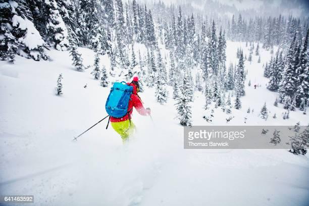 Woman skiing fresh snow to partner waiting at bottom of run while on backcountry ski tour
