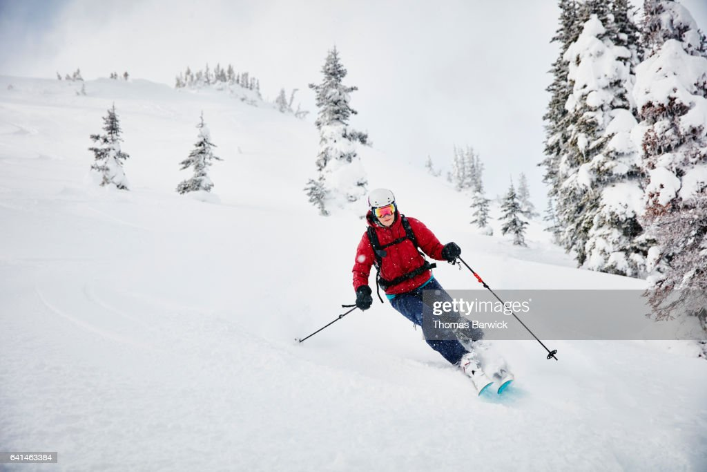 Woman skiing fresh snow while on backcountry ski tour : Stock Photo
