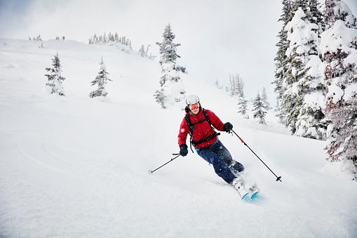 Woman skiing fresh snow while on backcountry ski tour - gettyimageskorea
