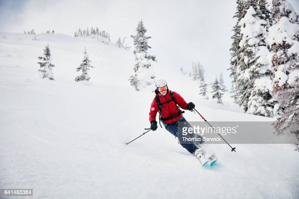 woman skiing fresh snow while on backcountry ski tour - winter sport stock pictures, royalty-free photos & images
