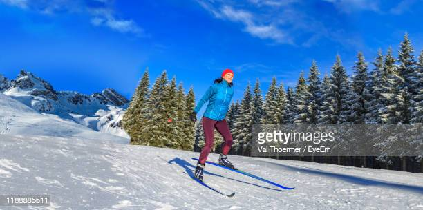 woman skiing on ice at mountain slope against sky - val thoermer stock-fotos und bilder