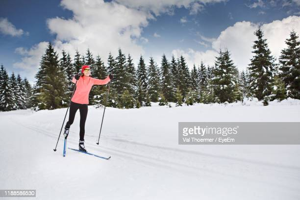 woman skiing on snow covered land - val thoermer stock-fotos und bilder