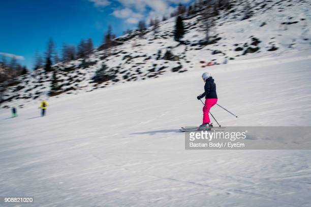 Woman Skiing On Snowcapped Mountain Against Sky