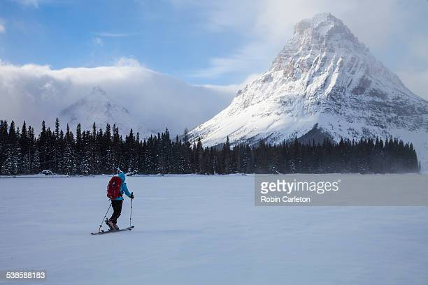 a woman skiing on two medicine lake in front of sinopah mountain and painted tepee peak in glacier national park, montana. - two medicine lake montana stock-fotos und bilder