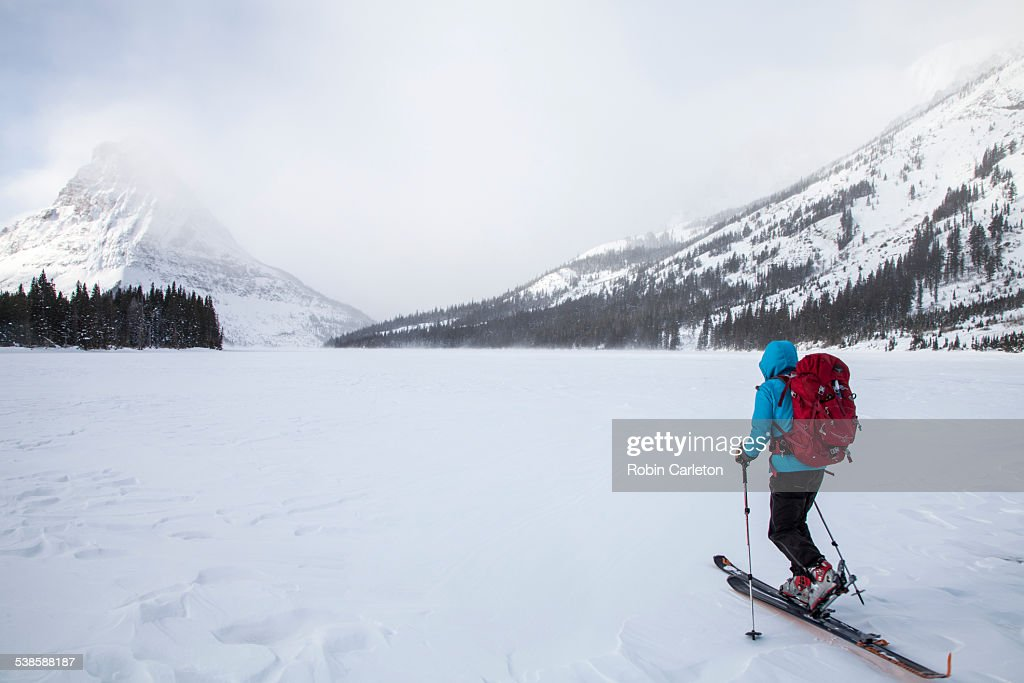 A woman skiing on Two Medicine Lake in front of Sinopah Mountain in Glacier National Park, Montana. : Stock Photo