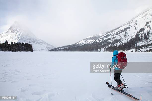 a woman skiing on two medicine lake in front of sinopah mountain in glacier national park, montana. - two medicine lake montana stock-fotos und bilder