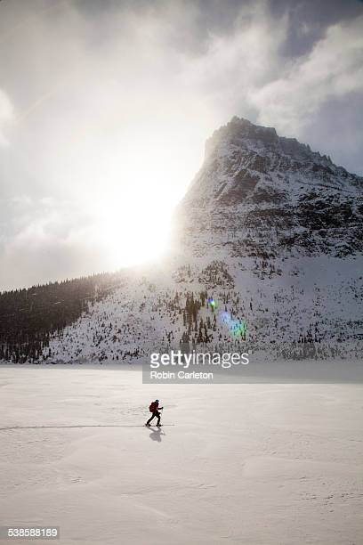 a woman skiing on two medicine lake in front of sinopah mountain in glacier national park, montana. - lago two medicine montana - fotografias e filmes do acervo