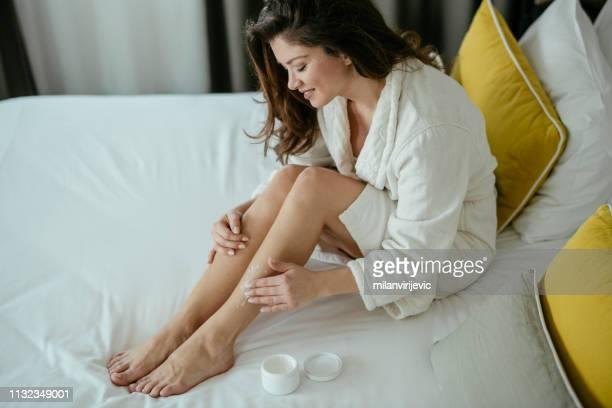 vrouw, huidverzorging, room, slaapkamer. vrouw die haar benen thuis verzorgt - vochtinbrengende crème stockfoto's en -beelden