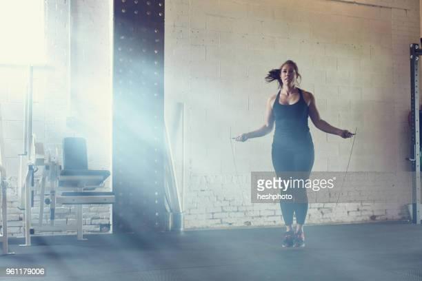 woman skipping in gym - heshphoto stock-fotos und bilder