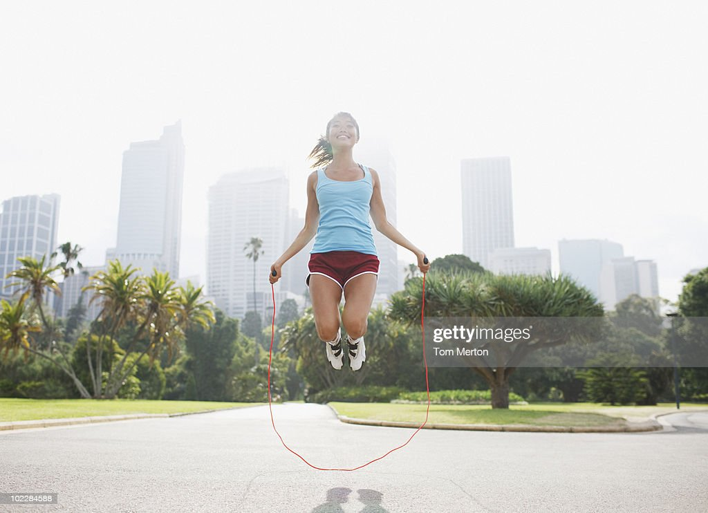 Woman skipping rope in park : Stock Photo