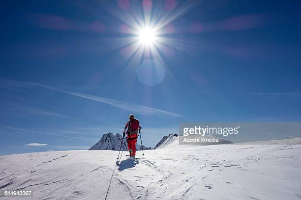 Woman skis to snow crest above mountains