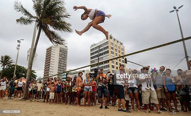 A woman slacklines on Ipanema beach during Carnival festivities on February 15 2015 in Rio de Janeiro Brazil This year's official Carnival...