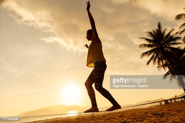 Woman Slacklining On Rope At Beach Against Sky During Sunset