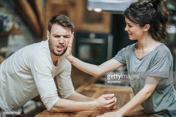 woman slapping her boyfriend for making a mistake at home. - slapping stock pictures, royalty-free photos & images