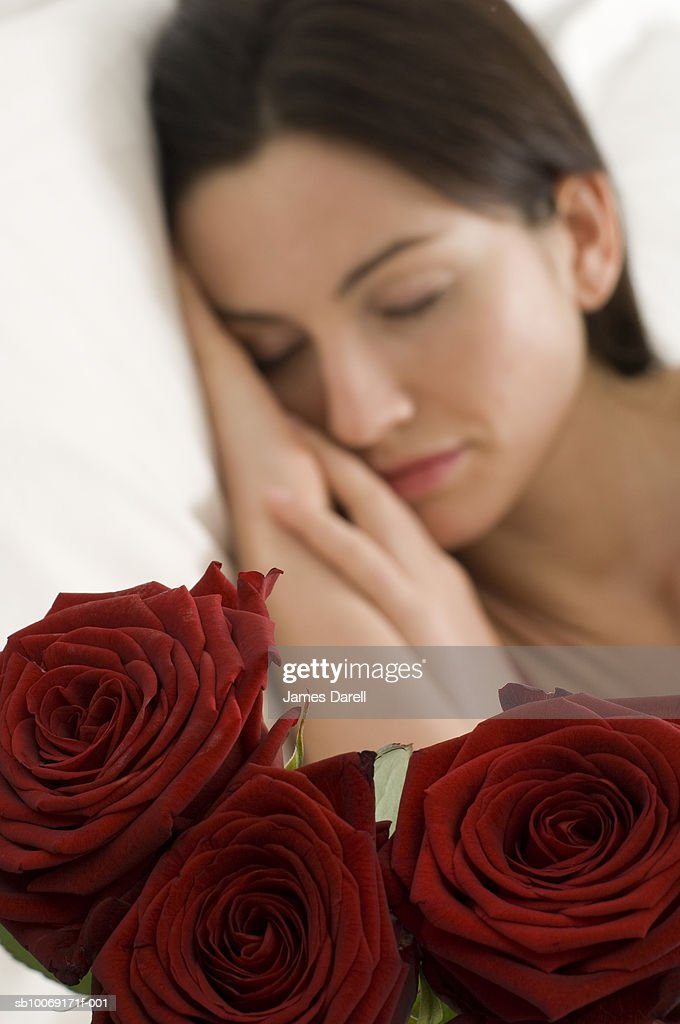 Woman sleeping, focus on roses in foreground : Stockfoto