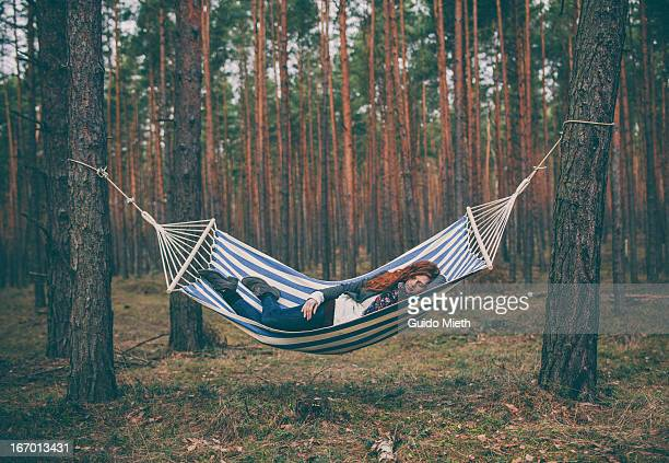 Woman sleeping in a hammock in the wood.