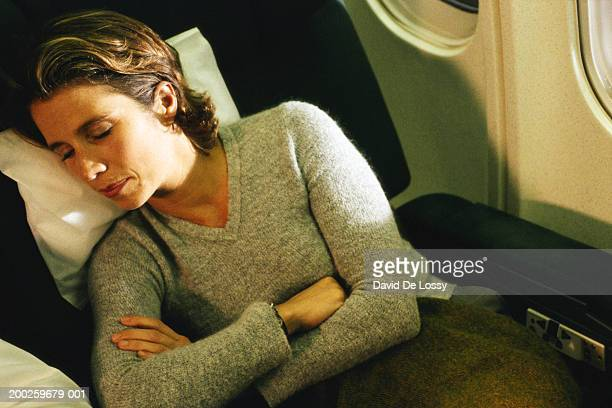 Woman sleeping in airplane with arms crossed, close-up